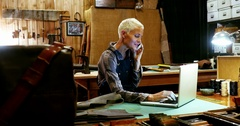 Craftswoman using laptop while talking on mobile phone Stock Footage