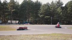 Kart drivers moving on a go kart track passing by the camera Stock Footage
