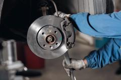 Change the old drive to the Brand new brake disc on car in a garage. Auto Stock Photos