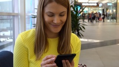 Young beautiful woman with smartphone in mall. Browsing internet, communicating Stock Footage