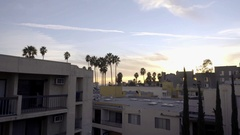 Los Angeles housing complex with balconies and terraces - palm trees and sunset Stock Footage
