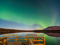 Northern Lights refecting off a calm lake with a dock in the foreground Stock Footage