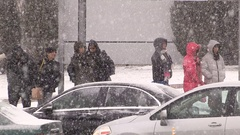 Transit riders waiting in snowstorm at bus stop Stock Footage