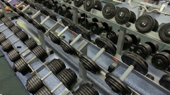 Set of dumbbells. View of rows of dumbbells on a rack in a gym. Stock Footage