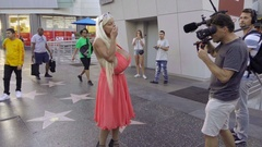 Blonde with busty breast implants blowing kiss film crew camera on Walk of Fame Stock Footage