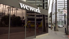WeWork sign on building panning Hollywood Boulevard street and cars in LA Stock Footage