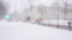 Snowfall in town with blurred moving cars on background Stock Footage