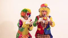 A couple of glad funny clowns playing and singing, when the toy frightens them Stock Footage