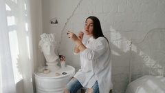 Plesant Girl doing makeup. White Home interior Stock Footage