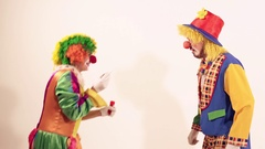 Happy young clown showers spray of soap bubbles over another circus clown Stock Footage