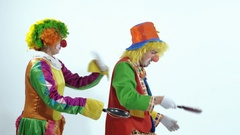 Two circus clowns throwing up a toy- pancake and catching it usin frying pans Stock Footage