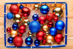 Straw basket packed full of multi-colored Christmas balls top view Stock Photos