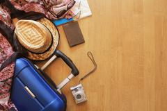 Suitcase and tourist stuff on wooden background Stock Photos
