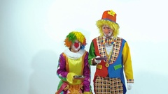 Two smiling circus clowns throwing up toy-pancakes, they cannot catch both of Stock Footage