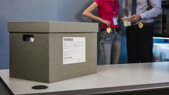 On the table is a box with material evidence, detectives on the background Stock Footage