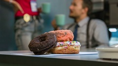 Donuts large in the foreground, in the background policemen drinking coffee. Stock Footage