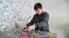 Teen Boy assembles the electrical circuit from constructor Stock Footage