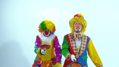A couple of circus clowns playing with pancakes and frying pans Stock Footage
