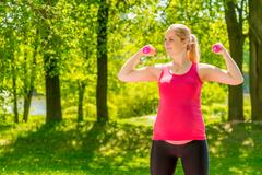 Strong athletic woman expecting a baby. Going for sports park Stock Photos