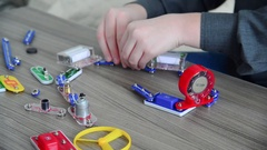 Boy assembles the electrical circuit from constructor Stock Footage