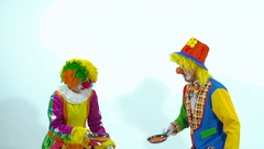 A couple of circus clowns throwing up toy-pancakes and trying to catch them Stock Footage