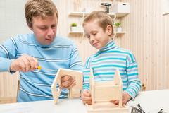 Father shows his son how to build a bird feeder Stock Photos