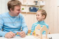 Father and son preschooler build a wooden bird feeder Stock Photos