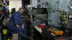 TV serviceman sits and analyses broken TV at the cluttered workshop by Sheyno. Stock Footage