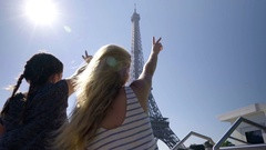 Young Women Hold Up Peace Signs As They Pass The Eiffel Tower In Paris, France Stock Footage