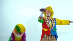 Portrait of two young comic clowns having fun together playing with toy-pans Stock Footage