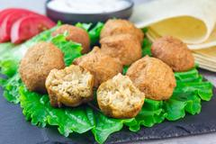 Chickpea falafel balls on slate board with vegetables and sauce Stock Photos