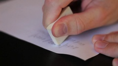 Erasing written from a paper with rubber Stock Footage