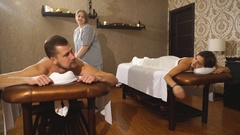 A young couple holds hands during a couples massage Stock Footage