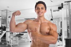 Muscles biceps bodybuilder bodybuilding gym flexing strong muscular young man Stock Photos