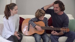 Father teaching his son and daughter how to play guitar Stock Footage
