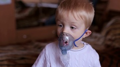 Adorable toddler boy making inhalation with nebulizer. Stock Footage
