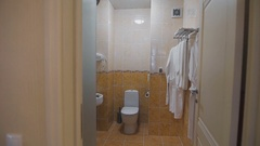 Bathroom with sink, toilet, mirror and white towels and bathrobes that hang on a Stock Footage