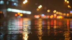 Colorful traffic lights bokeh circles reflecting in water on night city street Stock Footage