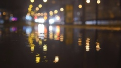 Slow motion lights bokeh circles reflecting in water on night city street Stock Footage