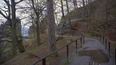 Footpath with railing for hikers, rainy wet forest mountain, Bastei, Germany Stock Footage