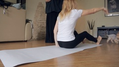 Woman in white shirt, black leggings lies on large sheet of paper Stock Footage