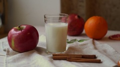Fruits and milk glass on kitchen table. Healthy breakfast. Fresh apple Stock Footage