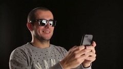 Man using smartphone smiling and typing message in black sudio indoors Stock Footage