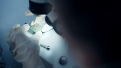 Professional scientist holding and observing the micro chip Stock Footage