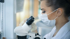Female scientist looking through a microscope in laboratory Stock Footage