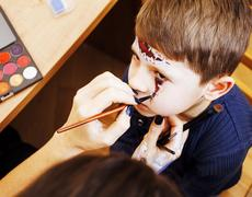 Little cute child making facepaint on birthday party, zombie Apo Stock Photos