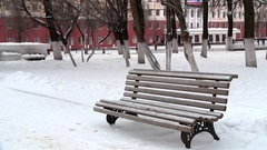 Empty snowy bench in the Park on a winter afternoon Stock Footage