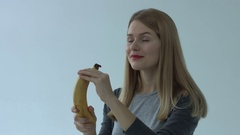 Beautiful young woman with red lips eating banana isolated on white background Stock Footage