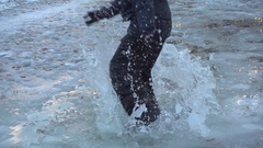 Boy jumping on icy puddle, slow motion 250 fps Stock Footage