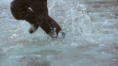 Boy running on icy puddle, slow motion 250 fps Stock Footage